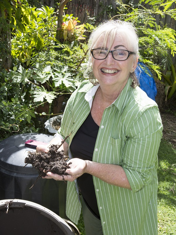 Lori smiles in her garden holding composted dirt in her hands