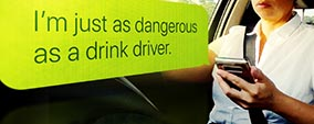 A driver on her mobile phone with the text 'I'm just as dangerous as a drink driver'