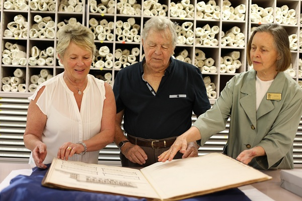 3 people looking at large book together