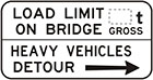 white sign with black arrow and text, load limit on bridge, number of tonnes gross. Heavy vehicles detour