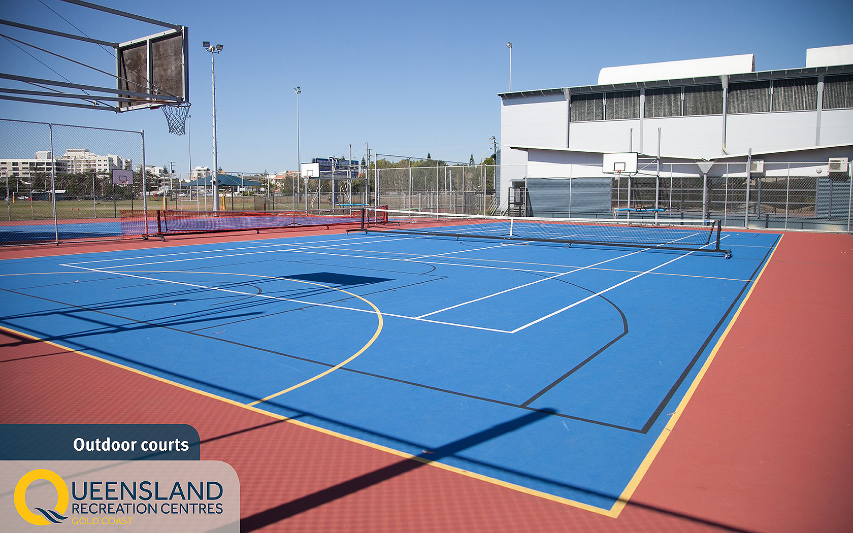 Fence-enclosed outdoor courts with multi-sport line markings set up for tennis at the Gold Coast Recreation Centre