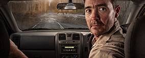 A person in a car has a flooded road in front of them. He is looking over his shoulder and a car is in his rear vision mirror.