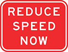 red sign with white text, reduce speed now