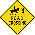 yellow diamond-shaped sign with black icon of a person riding a horse and a person hiking, as well as text, road crossing