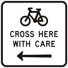 white sign with black icon of a bicycle, the words cross here with care, and an arrow