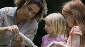 Ranger showing children a snake skin.