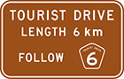 brown sign with white text, tourist drive length 6km follow route number