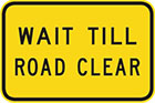 yellow sign with black text, wait till road clear