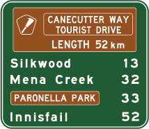green sign with white text list of locations and distances with brown panels showing tourist drive info