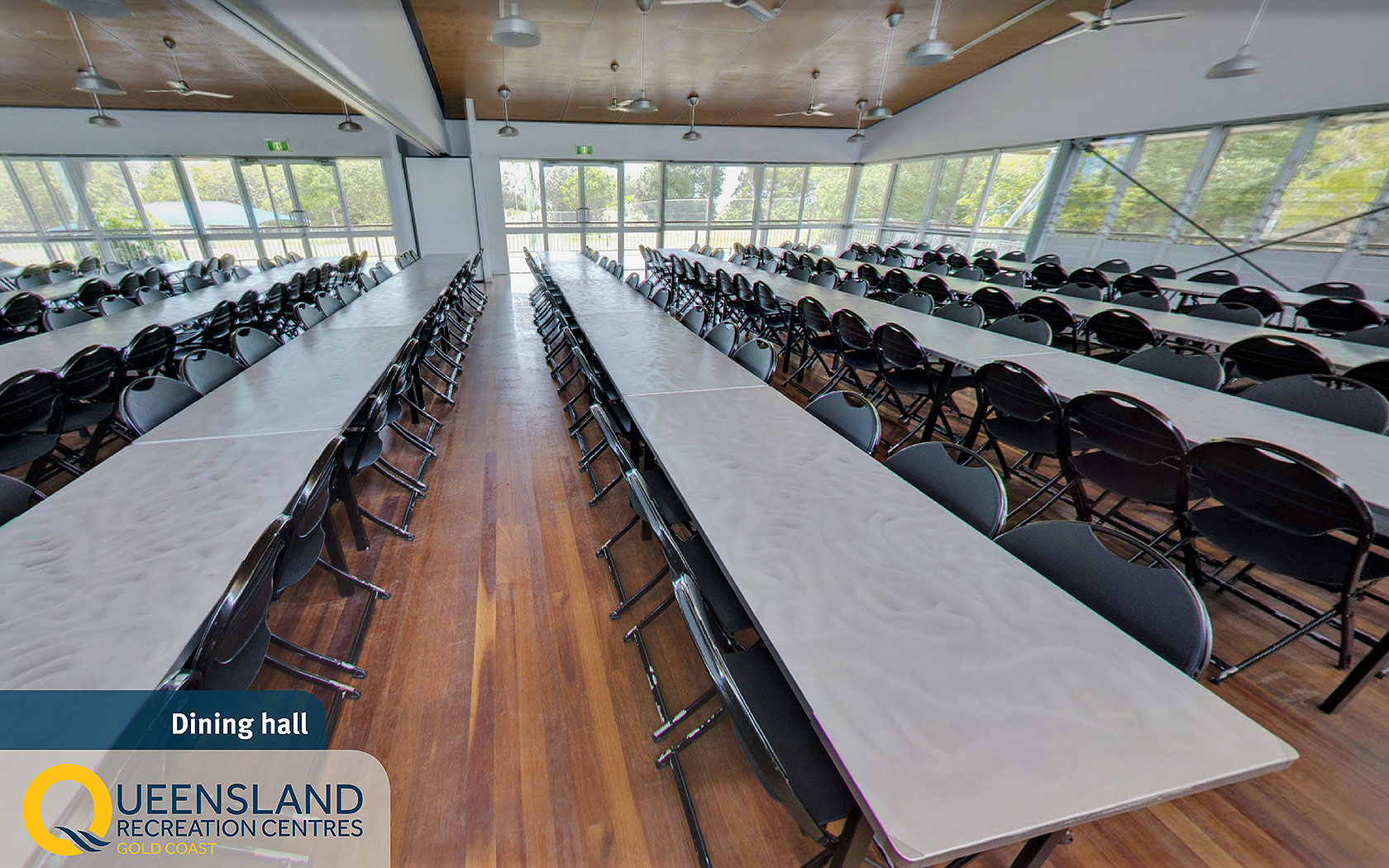 Spacious dining hall with long table and chair setup and overhead fans at the Gold Coast Recreation Centre