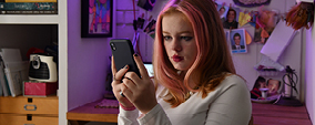 Teenage girl looking at her mobile phone screen.