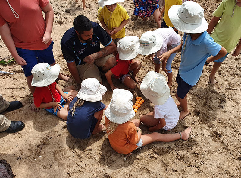 Photo of group of young students digging in the sand.