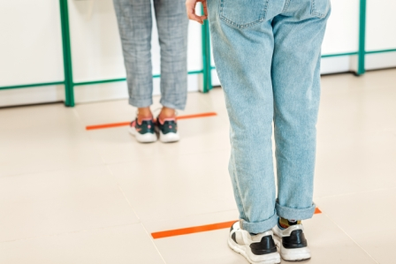 line of people standing a distance apart, lines marked on floor with tape