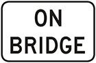 white sign with black text, on bridge