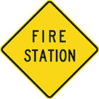 yellow diamond-shaped sign with black text, fire station