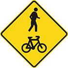 yellow diamond-shaped sign with a black icon of a human figure walking and a bicycle