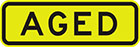 yellow sign with black text, aged