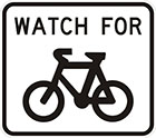 white sign with black words watch for, and an icon of a bicycle