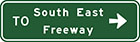 green sign with white arrow and text, to South East Freeway