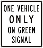 white sign with black text, one vehicle only on green signal