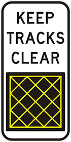 white sign with black text, keep tracks clear, and a black square panel with yellow cross hatching