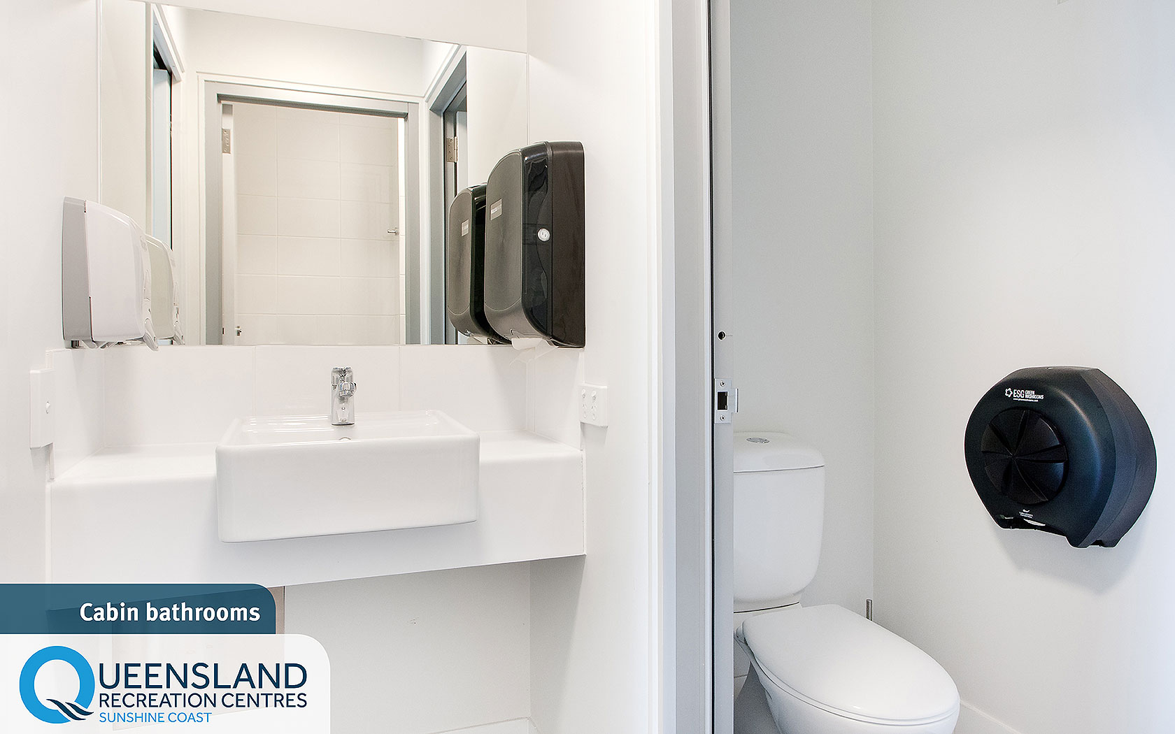 Standard cabin bathroom with toilet, sink, mirror and accessible dispensers at the Sunshine Coast Recreation Centre
