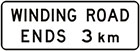 white sign with black text, winding road ends 3km