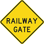 yellow diamond-shaped sign with black text, railway gate