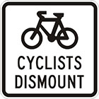 white sign with black icon of a bicycle and the words cyclists dismount