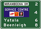green sign with white panel with black text, Mirambeena Dr, distances listed in white and a blue panel with the words service centre and 3 company logos