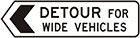 white sign with black arrow and text, detour for wide vehicles