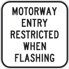white sign with black text, motorway entry restricted when flashing
