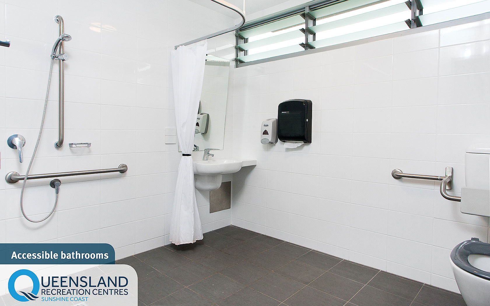 Accessible cabin bathroom with spacious shower, hand rails and accessible dispensers at the Sunshine Coast Recreation Centre