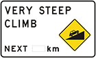 white sign with inset yellow diamond-shaped sign of black car driving up slope, as well as black text, very steep climb next number of km