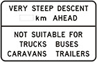 white sign with black text, very steep descent number of km ahead. Not suitable for trucks buses caravans trailers