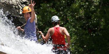 Two women rock climbing in a waterfall.
