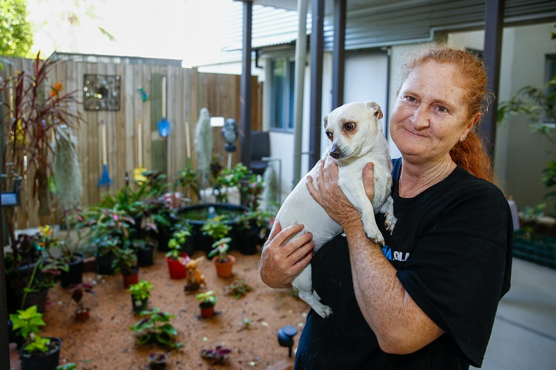 Cherrie in her garden holding her small dog