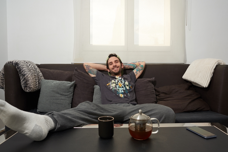 person sitting on a couch looking relaxed and eating from a bowl