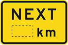 yellow sign with the word next in black, and space for a distance in km or m