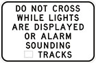 white sign with black text, do not cross while lights are displayed or alarm sounding, number of tracks