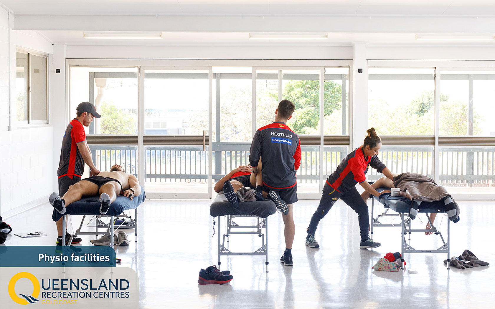 Athletes receiving physiotherapy treatments on massage tables at the Gold Coast Recreation Centre