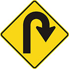 yellow diamond-shaped sign with black arrow that turns right into a u-shape