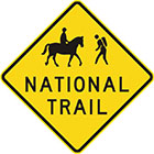 yellow diamond-shaped sign with black icon of a person riding a horse and a person hiking, as well as text, national trail