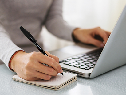 Close up photo of person using a laptop and taking notes on a notepad