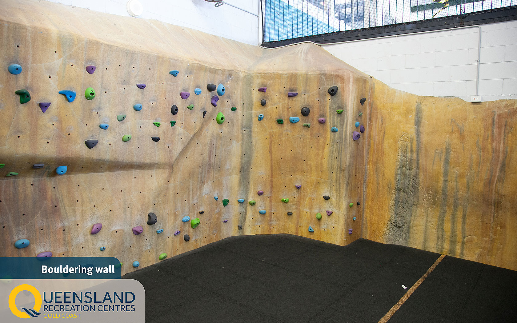 Single-storey bouldering wall with colourful hand holds at the Gold Coast Recreation Centre
