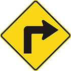 yellow diamond-shaped sign with black arrow that bends to the right at a right angle