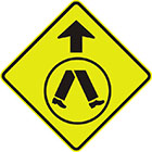 yellow diamond-shaped sign with black arrow and inset sign image of legs walking