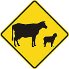 yellow diamond-shaped sign with black icons of a cow and a sheep