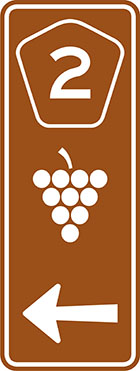 brown sign with pentagonal route number badge, grapes icon and an arrow
