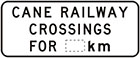 white sign with black text, cane railway crossings for number of km
